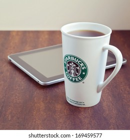 PETAH TIKVA, ISRAEL- JANUARY 3, 2014: Photo of Starbucks coffee cup and Apple iPad device on wooden table.Starbucks Corporation is an American global coffee company and coffeehouse chain.