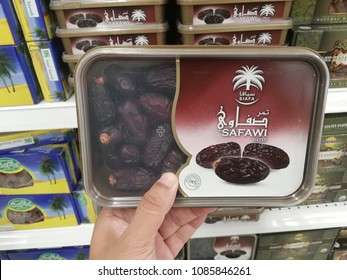 petaling jaya - malaysia, 23 april 2018: hand holding fresh safawi dates fruit from siafa brand for selling in market