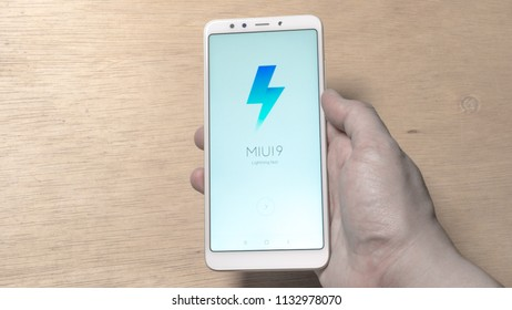 Petaling Jaya, Malaysia - July 11, 2018. Consumer holding smartphone with MIUI logo on screen. MIUI is a stock and aftermarket firmware for smartphones and tablet computers, developed by Xiaomi.