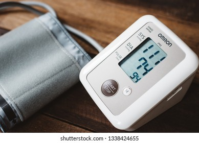 Petaling Jaya, Selangor, Malaysia - 14 March 2019 : Sphygmomanometer or electronic blood pressure from brand OMRON on a wooden desk. Omron is a well known company in manufacturing medical instrument