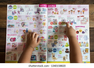"Petaling Jaya, Selangor, Malaysia - 16 March 2019 : Child hand pointing at her dream toy on a TOYS ""R""US brochure, asking for a birthday gift. toys r us is a famous company selling toys."