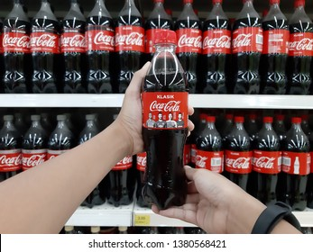 Petaling Jaya, Selangor, Malaysia - 25 April 2019 : Customer hand holding a COCA-COLA bottled drink against supermarket shelves. COCA-COLA is a famous cola drink.