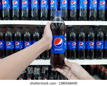 Petaling Jaya, Selangor, Malaysia - 25 April 2019 : Customer hand holding a PEPSI bottled drink against supermarket shelves. Pepsi is a famous cola drink.