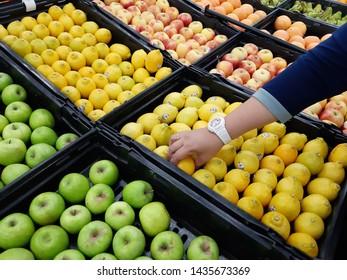 petaling jaya,selangor,malaysia - 25 march 2019 : customer choosing an  apples and lemon in a display basket inside a supermarket