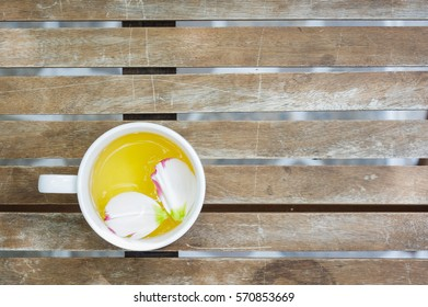 Petals of Eustoma russellianum flower in tea cup on wooden table