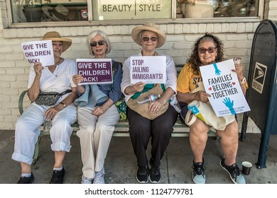 Petaluma, CA/USA-June 30, 2018: Four ladies sit on a bench holding signs during Keep Families Together March