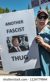 Petaluma, CA/USA-June 30, 2018: Man holds sign comparing President Trump with Hitler and Mussolini, calling them fascist thugs, during Keep Families Together March