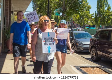 Petaluma, CA/USA-June 30, 2018: People march along sidewalk with signs during Keep Families Together March
