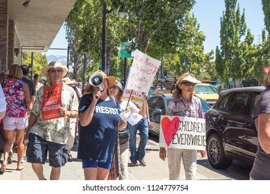 Petaluma, CA/USA-June 30, 2018: People carry signs and a woman uses bullhorn during Keep Families Together March