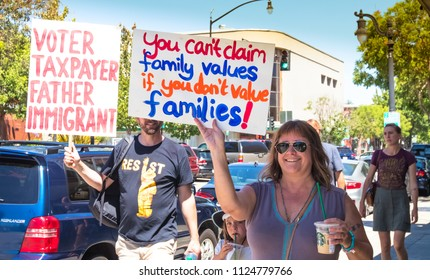 Petaluma, CA/USA-June 30, 2018: People walk on the sidewalk holding signs during Keep Families Together March