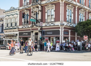Petaluma, CA/USA-June 30, 2018: People cross the street carrying signs during Keep Families Together March