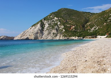 Petani Beach, Kefalonia, Greece. Beautiful beach with white stones and turquoise water on Kefalonia island (Ionian island) in Greece with rock in the background. Amazing Landscape. World famous beach.