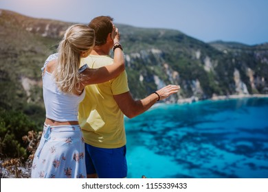 Petani view point young woman closing her boyfriend eyes in front of gorgeous seascape panorama. Turquoise Petani beach on Kefalonia island Greece