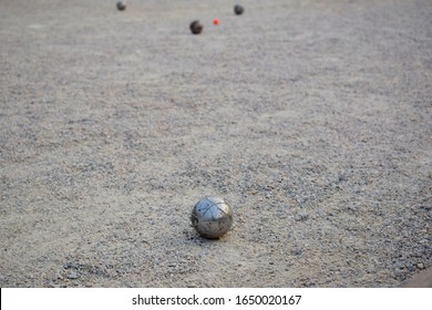 Petanque ball boules and small red jack on petanque field, Man playing petanque