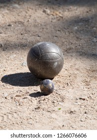 Petanque balls on the ground. Pétanque is a form of boules where the goal is to toss or roll hollow steel balls as close as possible to a small wooden ball called a cochonnet.