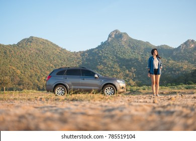 Petchburi ,Thailand -December 20 2017: women stand with private car for vacation, Gray color Chevrolet Captiva Photo with women on country road at 300 Yod Mountain,Thailand