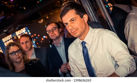 Pete Buttigieg standing in front of his husband looking upward. Wearing a white button down shirt with a thin blue tie.  Presidential Candidate for 2020 May 15 2019 Los Angeles grassroots fundraiser