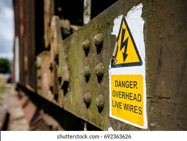 PETERBOROUGH, CAMBRIDGESHIRE, UK - CIRCA AUGUST 2017: Close-up view of a weathered yellow power cable warning sign, seen on the side of a derelict railway car located in a railway shunting yard.