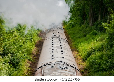 Peterborough, Cambridgeshire, UK - Circa June 2019: Railway bridge view of a famous, British steam locomotive seen pulling a number of passenger cars along a single track. Clouds of water seam is seen
