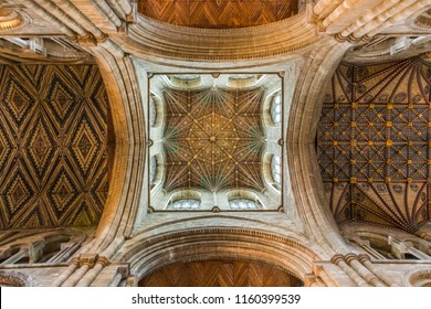 Peterborough, Cambridgeshire / UK - June 12 2018: Inside Peterborough Cathedral directly underneath the tower, looking up to the ceiling showing intricate woodworking, colours and gilt-work.
