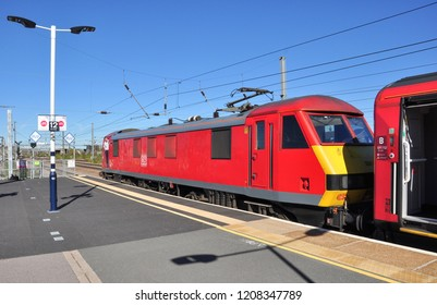 PETERBOROUGH, CAMBRIDGESHIRE/UK - September 27, 2018. Red liveried DB class 90 electric locomotive waits at the head of a northbound express, Peterborough, Cambridgeshire, England