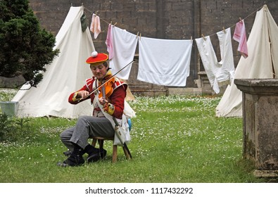 Peterborough, England - June 17, 2018:  A man dressed as an early 19th Century soldier plays violin in a Napoleonic encampment as part of the annual Peterborough Heritage Festival.