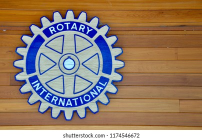 Peterborough, Ontario, Canada - August 31, 2018: Symbol of Rotary Club International in a wooden background.