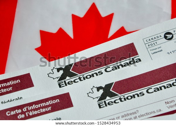 Peterborough, Ontario, Canada - October 8, 2019: Election Canada voter information cards over small Canadian flag.