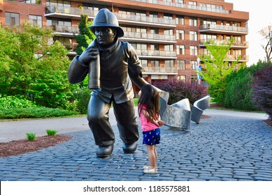 Peterborough, Ontario, Canada - September 13, 2018: Little girl is looking intently to momument of firefighter carrying a hose in Del Crary park in Peterborough.
