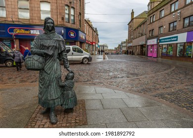 Peterhead, Scotland, UK - 05 February 2016: Sculpture of a woman with a little girl in the main square of the city. Cloudy day.