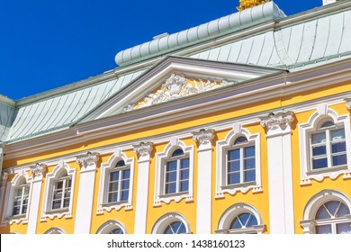 Peterhof, Russia, 05.18.2019. External wall with pilasters, pediment and roof of the Grand Palace in Peterhof against the blue sky