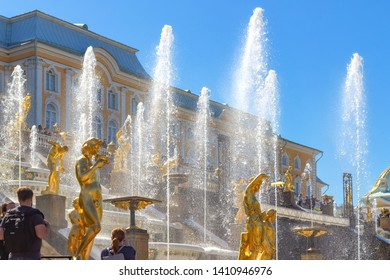 Peterhof, Russia, 05.18.2019. Fountains of the Grand cascade in Peterhof. Gilded statues, water jets and myriads of splashes against the background of Petrodvorets and blue sky