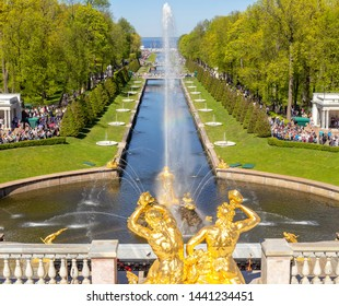 Peterhof, Russia, 05.18.2019. Sea channel and Golden sculptures of the Grand cascade in Peterhof. Groups of tourists on excursions to the sights of Peterhof