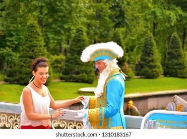 PETERHOF, RUSSIA 20.08. 2017. Young tourists want to be photographed with the model in an ancient court costume in the Peterhof park. Saint Peterbug, Russia