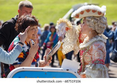 PETERHOF, RUSSIA - JULY 2, 2017. Asian tourists want to be photographed with the model in an ancient court costume in the Peterhof park. Saint Peterbug, Russia.