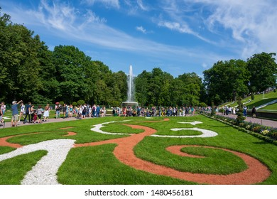 Peterhof, Russia -- July 21, 2019. Crowds of tourists walk around the  gardensand fountains at the Summer Palace in Peterhof.