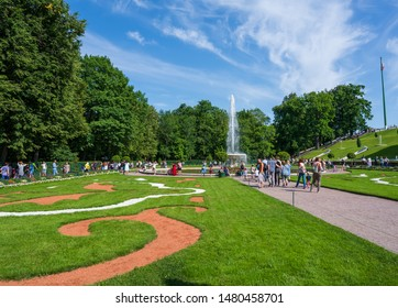 Peterhof, Russia -- July 21, 2019. Wide angle photo of tourists  walking around the  gardens at the Summer Palace in Peterhof.