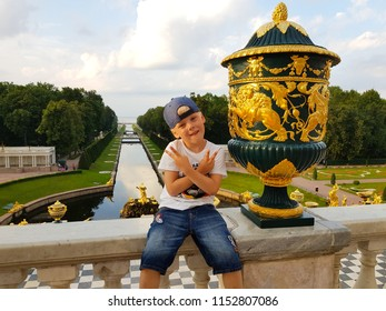 "Peterhof, Russia, July 26, 2018: A little boy sitting in the background of the Samson Fountain and Sea Channel.The Peterhof Palace sometimes referred as the ""Russian Versailles""."