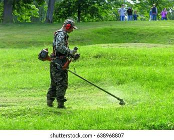Peterhof, Russia - June 22, 2016: Man is mowing grass by lawnmower in city park.
