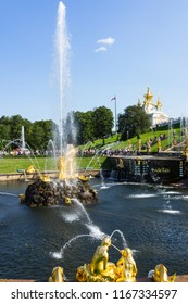 PETERHOF, SAINT PETERSBURG, RUSSIA - August 24, 2018: A round fountain of Great Cascade, called Scoop, is decorated with famous statue of Samson, in the foreground gilt sculptures of Siren
