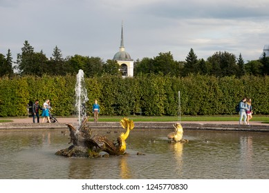 PETERHOF, SAINT-PETERSBURG, RUSSIA - SEPTEMBER 2, 2018: People walk near The Mezheumniy (Indefinite) Fountain in The Upper Garden. The State Museum Preserve Peterhof