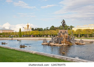 PETERHOF, SAINT-PETERSBURG, RUSSIA - SEPTEMBER 2, 2018: People walk in The Upper Garden. The Neptune Fountain. On the background is The Grand Palace and The Grand Palace Church of St Peter and Paul
