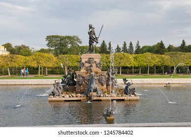 PETERHOF, SAINT-PETERSBURG, RUSSIA - SEPTEMBER 2, 2018: People walk in The Upper Garden near The Neptune Fountain. The Stae Museum Preserve Peterhof