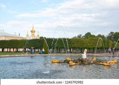 PETERHOF, SAINT-PETERSBURG, RUSSIA - SEPTEMBER 2, 2018: People take pictures near The Oak Fountain in The Upper Garden. On The background is The Grand Palace Church of St Peter and Paul