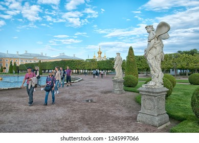 PETERHOF, SAINT-PETERSBURG, RUSSIA - SEPTEMBER 2, 2018: Tourists walk in The Upper Garden near Zephyrus and Vertumnus Statues. On the background is The Grand Palace and The Palace Church