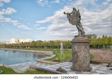 PETERHOF, SAINT-PETERSBURG, RUSSIA - SEPTEMBER 2, 2018: The Upper Garden. Apollo Belvedere Statue. On the background is The Palace Church of Saints Peter and Paul