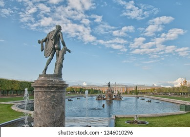 PETERHOF, SAINT-PETERSBURG, RUSSIA - SEPTEMBER 2, 2018: The Upper Garden. Apollo Belvedere Statue. On the background is The Neptune Fountain, The Grand Palace and Palace Church St Peter and Paul