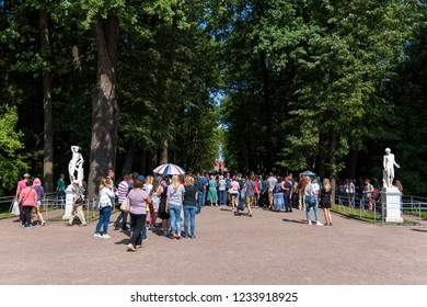 Peterhof, St. Petersburg, Russia - August 17, 2018: The laughing tourists in fountain-cracker in Peterhof