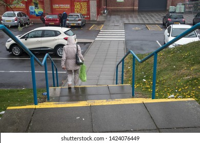 Peterlee / Great Britain - April 25, 2019 : Woman in raincoat with hood pulled up walking down stairway towards a car park in the rain