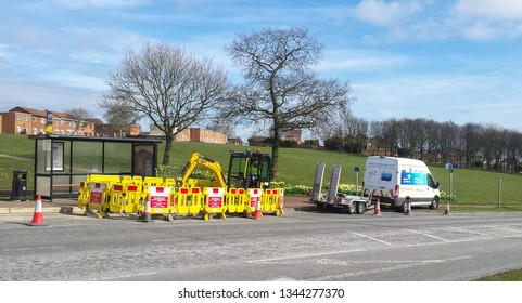 Peterlee / Great Britain - March 20, 2019: JCB style digger digging at the roadside surrounded by yellow barriers with Northern Gas Networks van and trailer.